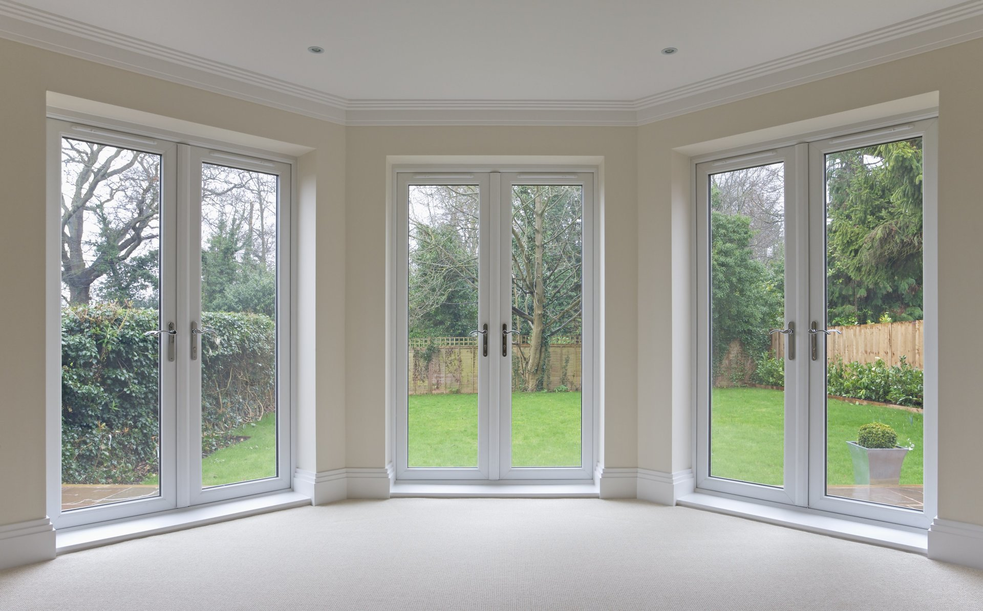 A bright room with glass doors revealing a green garden.
